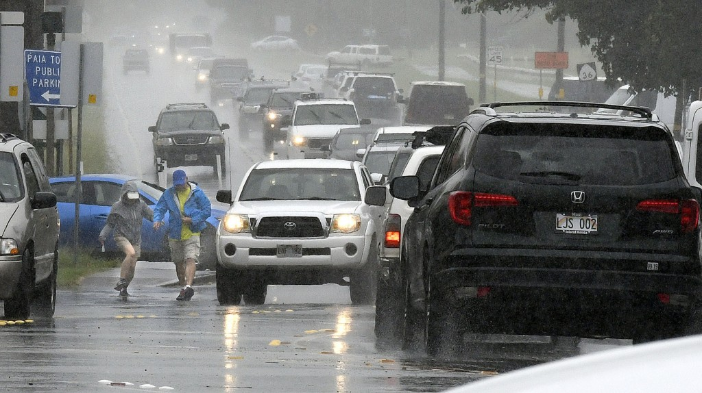 A couple walks in a rainstorm amid heavy traffic in Paia, Hawaii, on Tuesday, Sept. 11, 2018, as Tropical Storm Olivia marched closer to Maui. Olivia