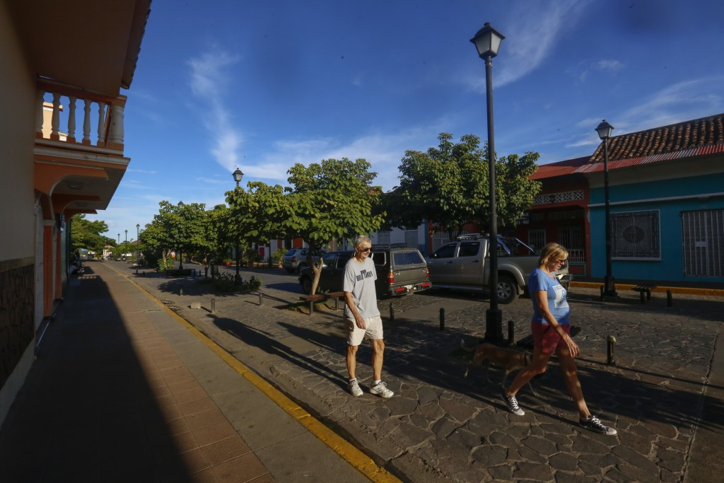 A couple of foreign tourists walk on La Calzada street in the colonial city of Granada, Nicaragua, Monday, Sept. 10, 2018. Economists estimate 200,000