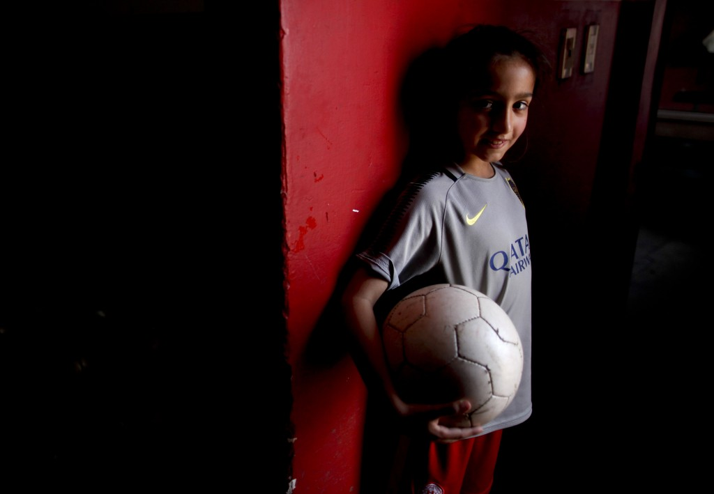 In this Sept. 8, 2018 photo, 7-year-old Candelaria Cabrera poses for a portrait holding a soccer ball in Chabaz, Argentina. She was 3 years old when h