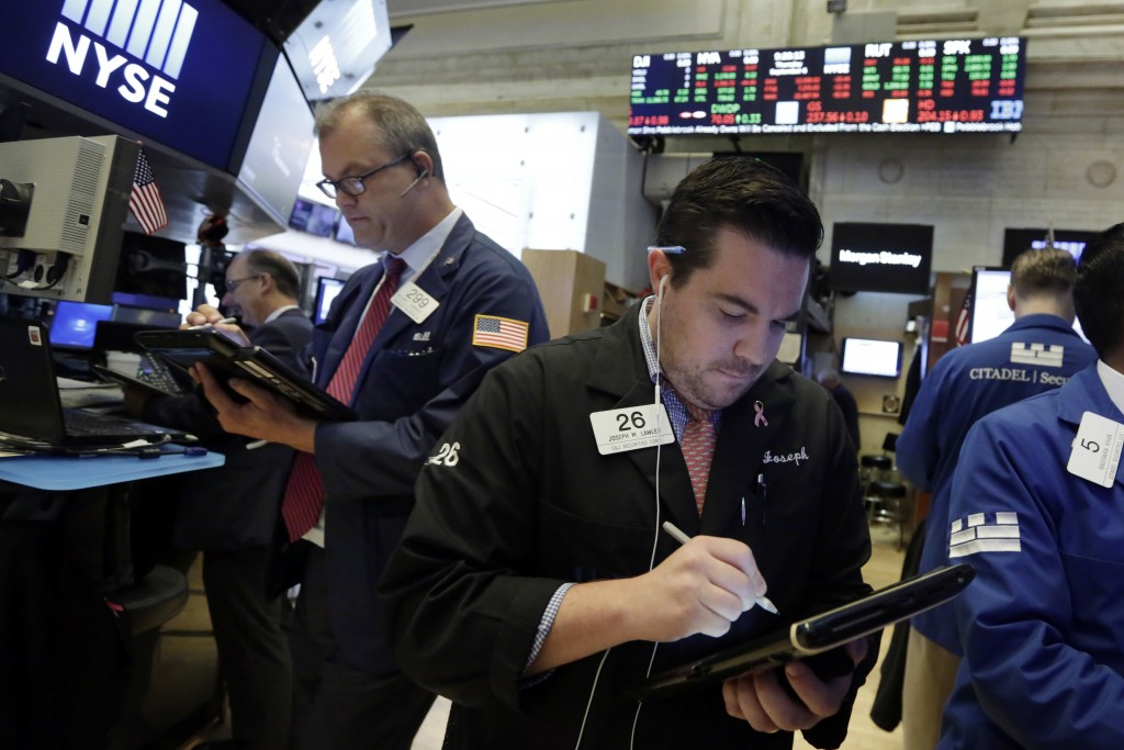 FILE- In this Sept. 6, 2018, file photo Joseph Lawler, right, works with fellow traders on the floor of the New York Stock Exchange. The U.S. stock ma...
