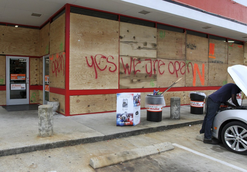 An auto parts store has wood paneling installed over the windows, Tuesday, Sept. 11, 2018, in New Bern, N.C., as a  precaution against storm damage fr