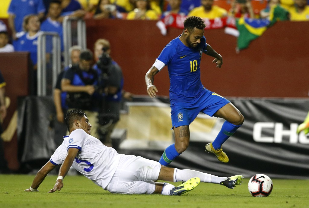 Brazil forward Neymar, right, dribbles over El Salvador defender Roberto Dominguez in the second half of a soccer match, Tuesday, Sept. 11, 2018, in L