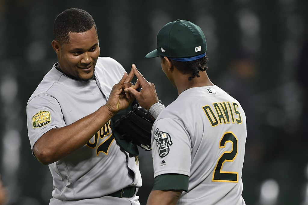 Oakland Athletics closer Jeurys Familia, left, and Khris Davis celebrate their 3-2 win over the Baltimore Orioles in a baseball game, Tuesday, Sept. 1