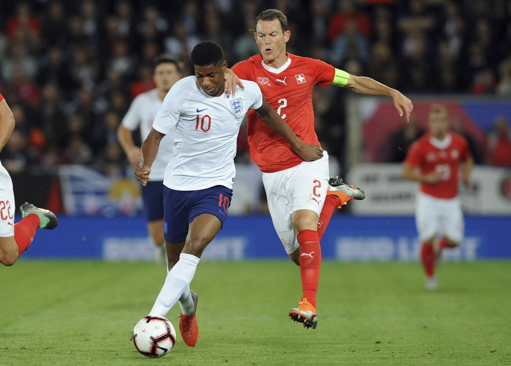 England's Marcus Rashford, left, and Switzerland's Stephan Lichtsteiner challenge for the ball during the International friendly soccer match between