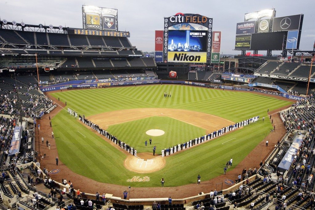 The Miami Marlins and the New York Mets joins members of the New York police and fire departments on the field for pregame ceremonies before a basebal
