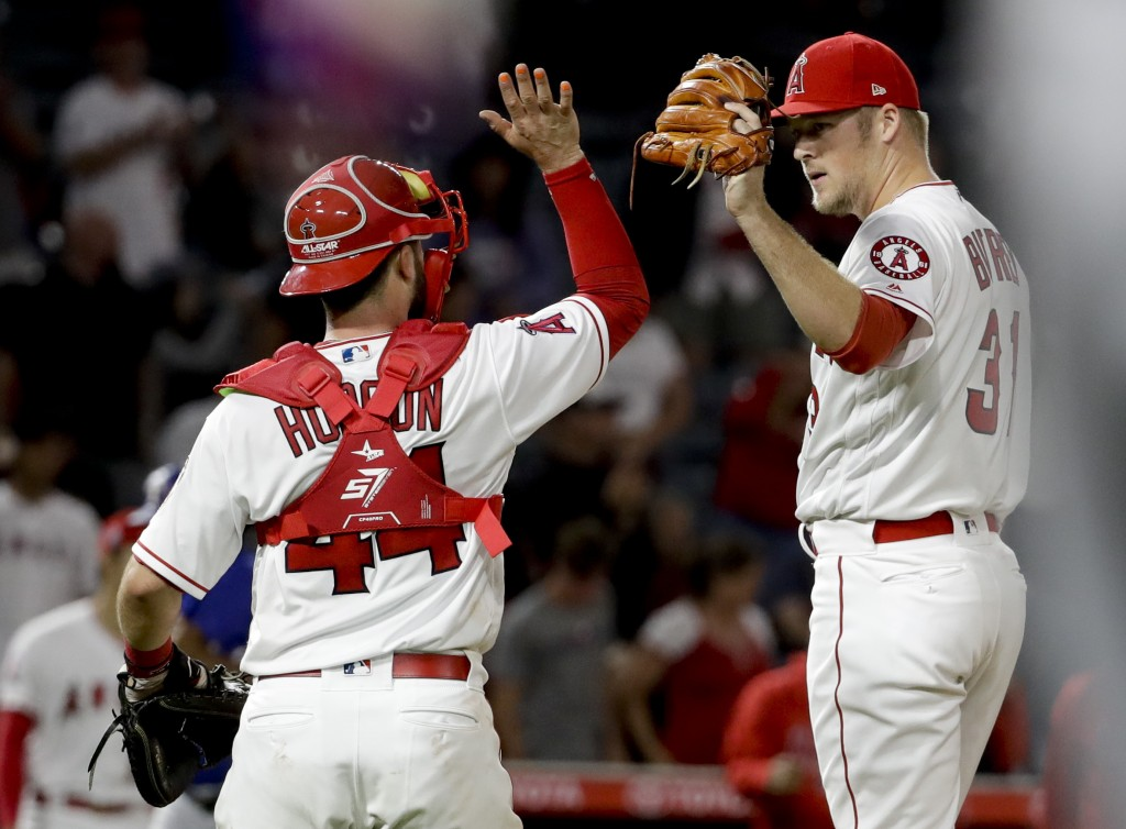 Los Angeles Angels catcher Joe Hudson and pitcher Ty Buttrey celebrate after their 1-0 win over the Texas Rangers after a baseball game in Anaheim, Ca
