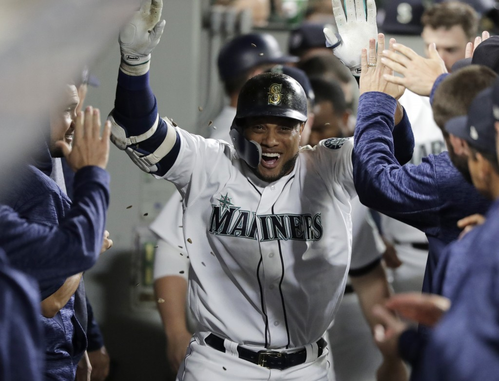 Sunflower seeds fly as Seattle Mariners' Robinson Cano is greeted in the dugout after he hit a solo home run against the San Diego Padres during the t