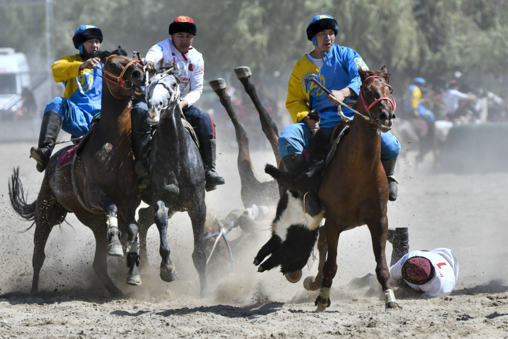 In this photo taken on Wednesday, Sept. 5, 2018, horse riders compete for the goat during a kok boru, also called ulak tartysh match between Russia an...