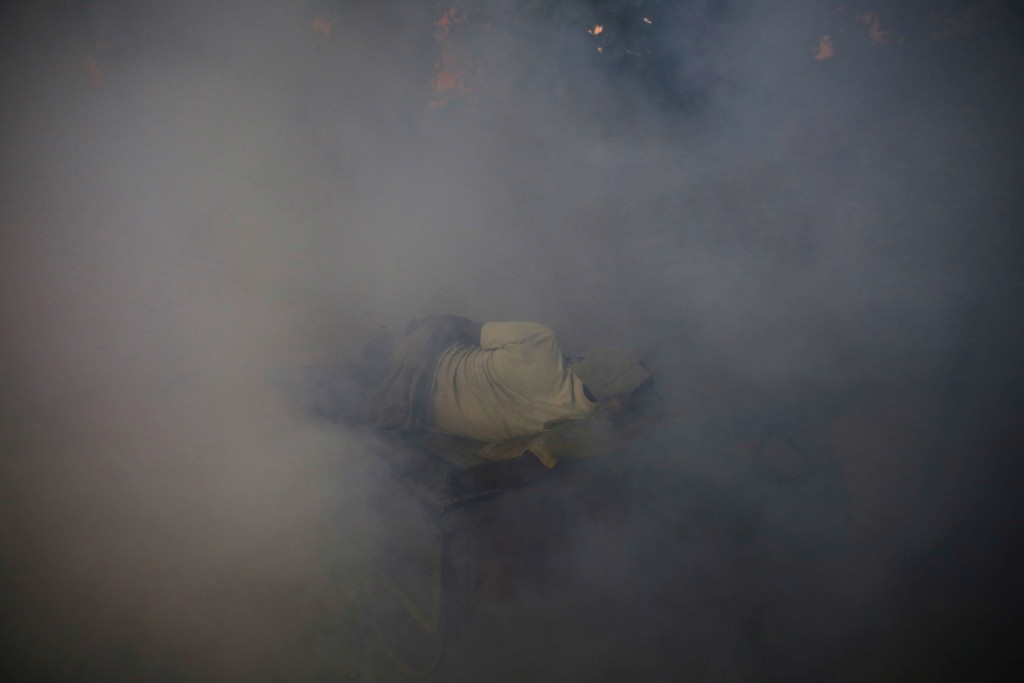 In this Thursday, Sept. 13, 2018, file photo, a man sleeps on a cart surrounded by smoke from fumigation, being carried out to prevent the spread of m