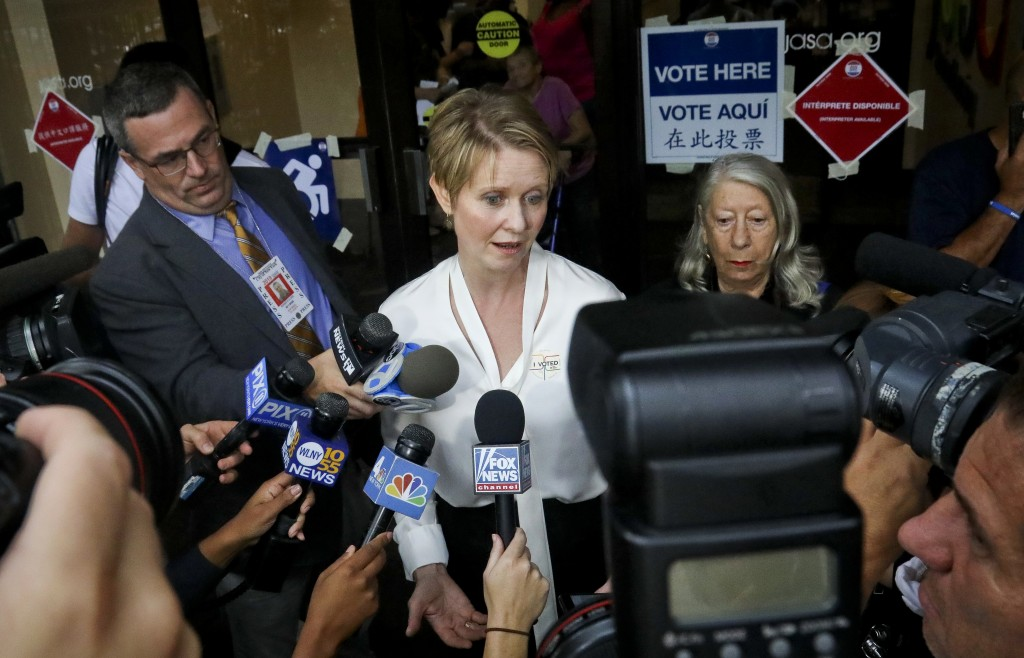 New York gubernatorial candidate Cynthia Nixon, center, speaks to members of the media outside a polling station after voting in the primary, Thursday