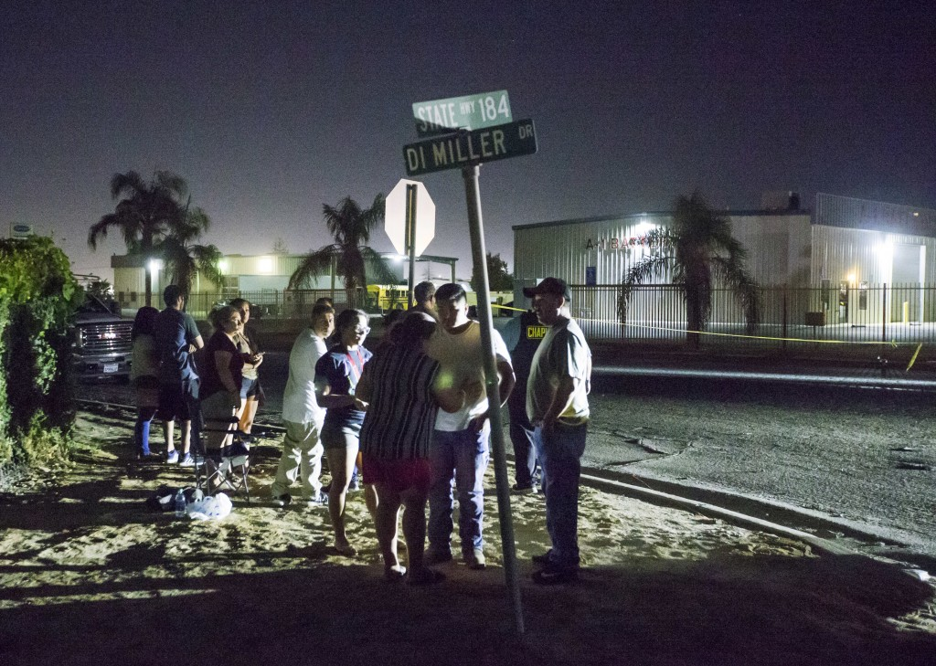 A crowd gathers near a location where a gunman opened fire, killing several people, Wednesday, Sept. 12, 2018, in Bakersfield, Calif. A gunman killed