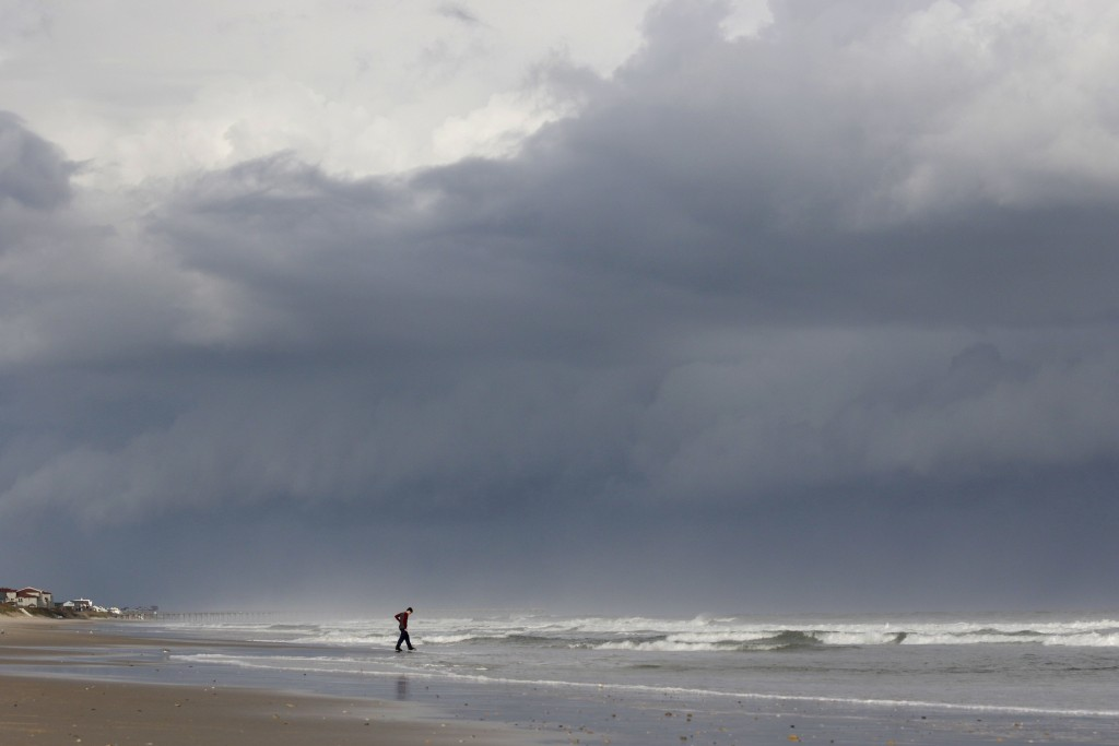 A storm front looms behind Seth Loconte as he walks on the beach in North Topsail Beach, N.C., prior to Hurricane Florence moving toward the east coas