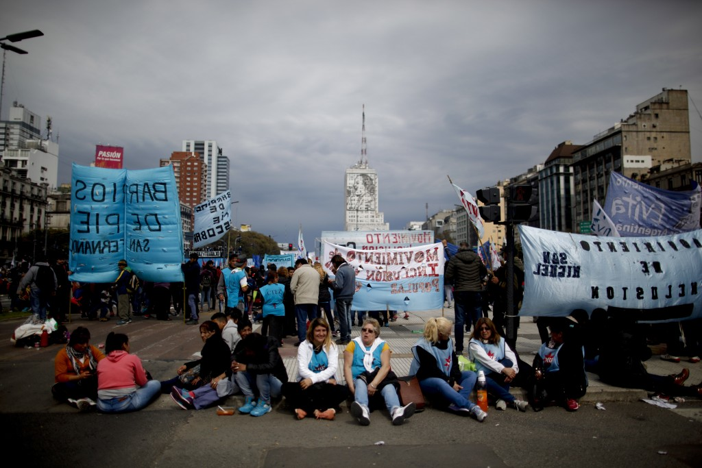Demonstrators sit in the middle of 9 de Julio avenue to protest new government economic measures in Buenos Aires, Argentina, Wednesday, Sept. 12, 2018