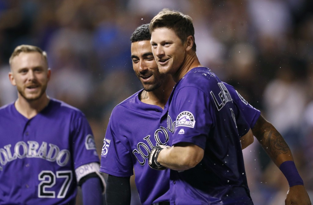 Colorado Rockies' DJ LeMahieu, right, is congratulated after hitting a two-run home run by Ian Desmond, center, and Trevor Story to defeat the Arizona