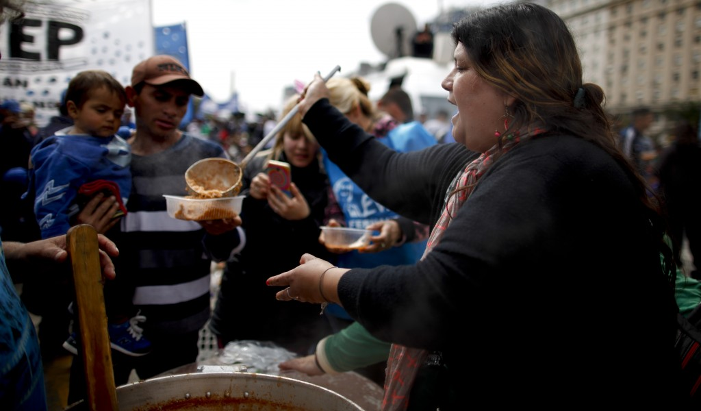 A woman serves meatballs and rice from a soup kitchen set up in the middle of 9 de Julio avenue as a protest against new government economic measures