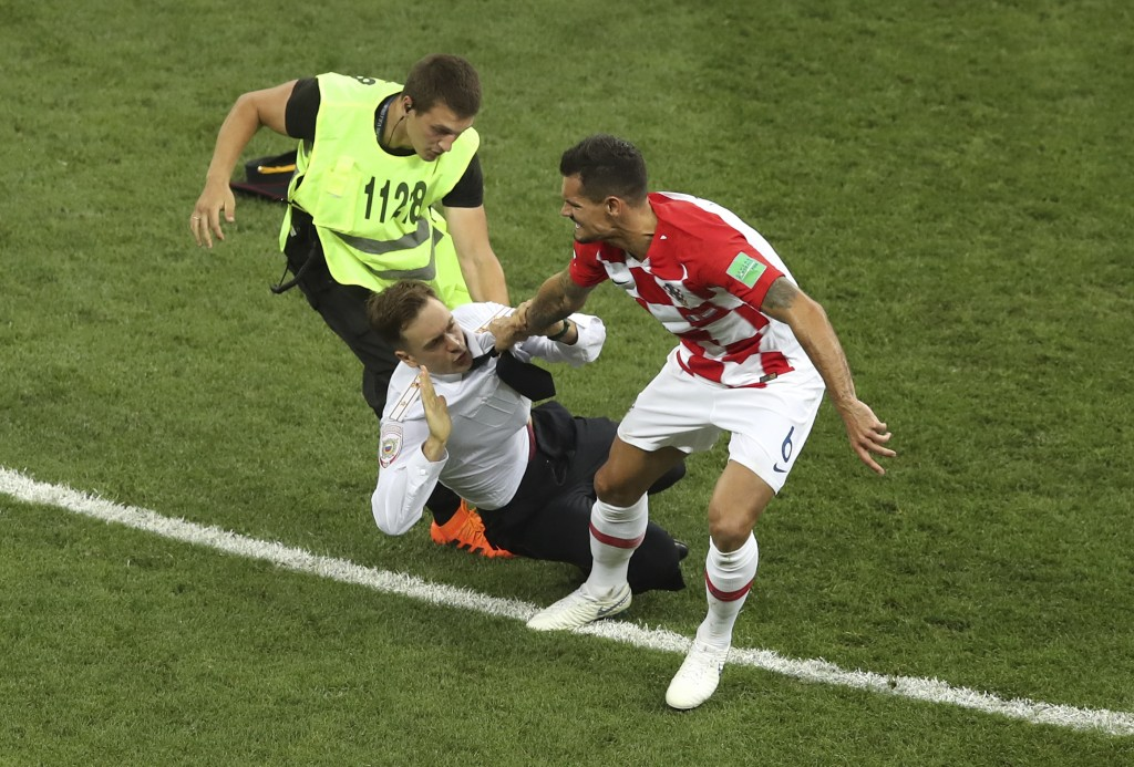 FILE - In this Sunday, July 15, 2018 file photo, Croatia's Dejan Lovren and a steward grab Pyotr Verzilov, who invaded the pitch during the France and