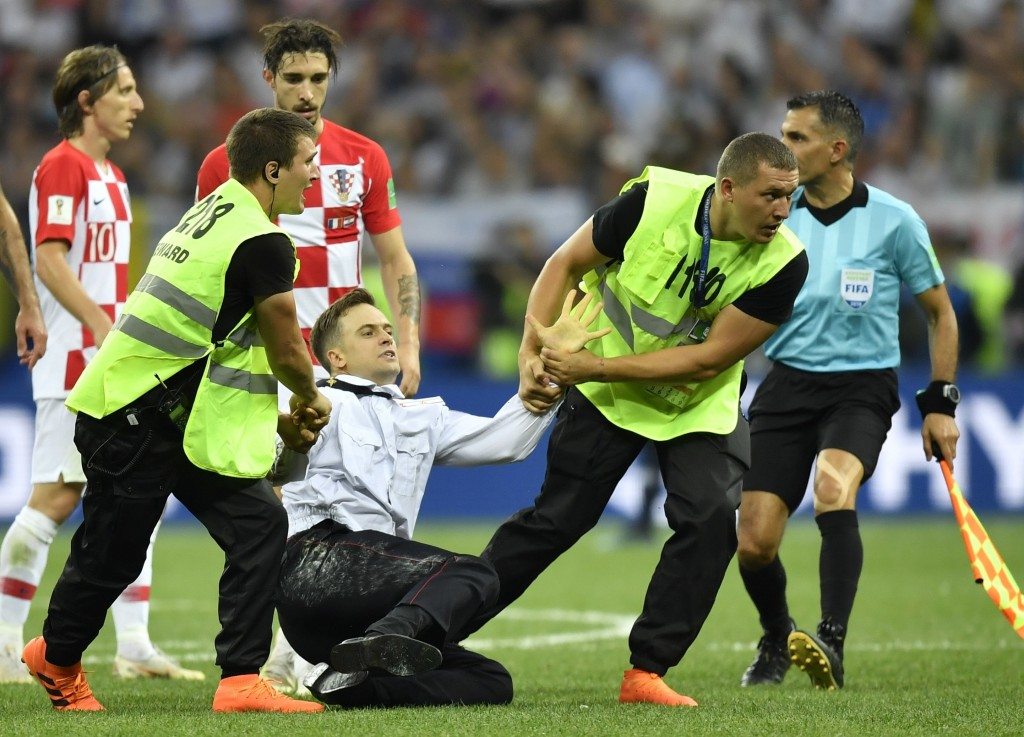 FILE - In this July 15, 2018, stewards pull Pyotr Verzilov, a member of the feminist protest group Pussy Riot off the pitch after he stormed onto the