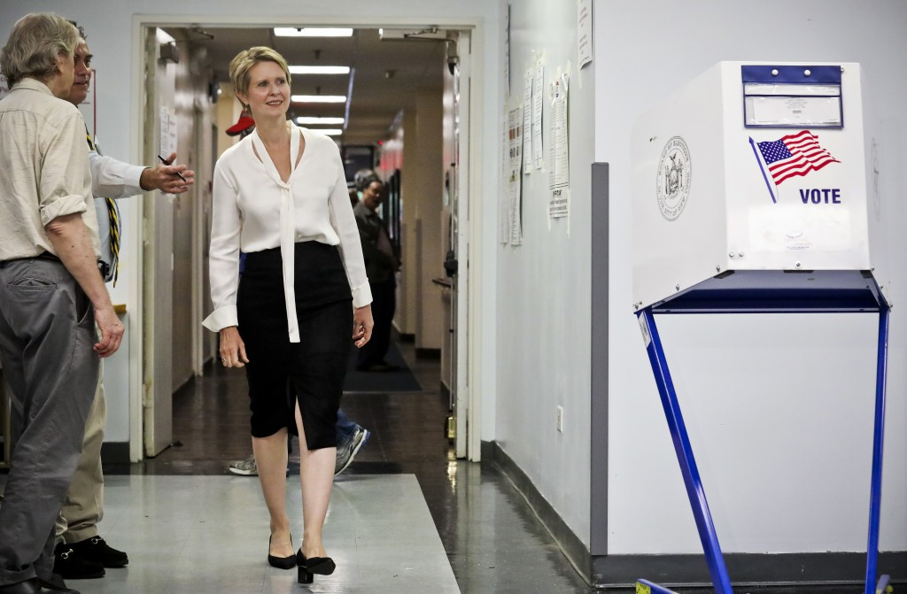 Polling station officials direct New York gubernatorial candidate Cynthia Nixon to her voting area for the primary, Thursday, Sept. 13, 2018, in New Y...