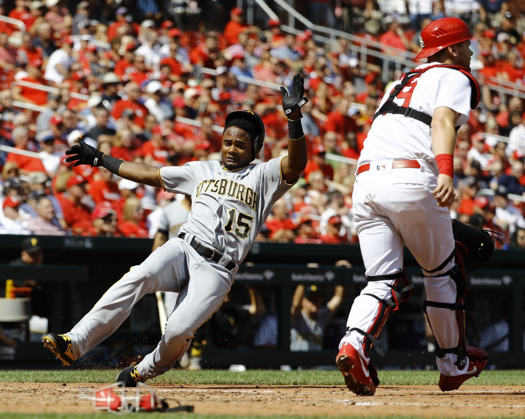 Pittsburgh Pirates' Pablo Reyes, left, slides in safely as St. Louis Cardinals catcher Carson Kelly waits for the throw during the sixth inning of a b...