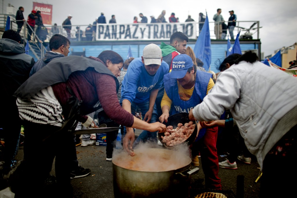 Protesters cook meatballs and rice in the middle of 9 de Julio avenue as a protest against new government economic measures in Buenos Aires, Argentina