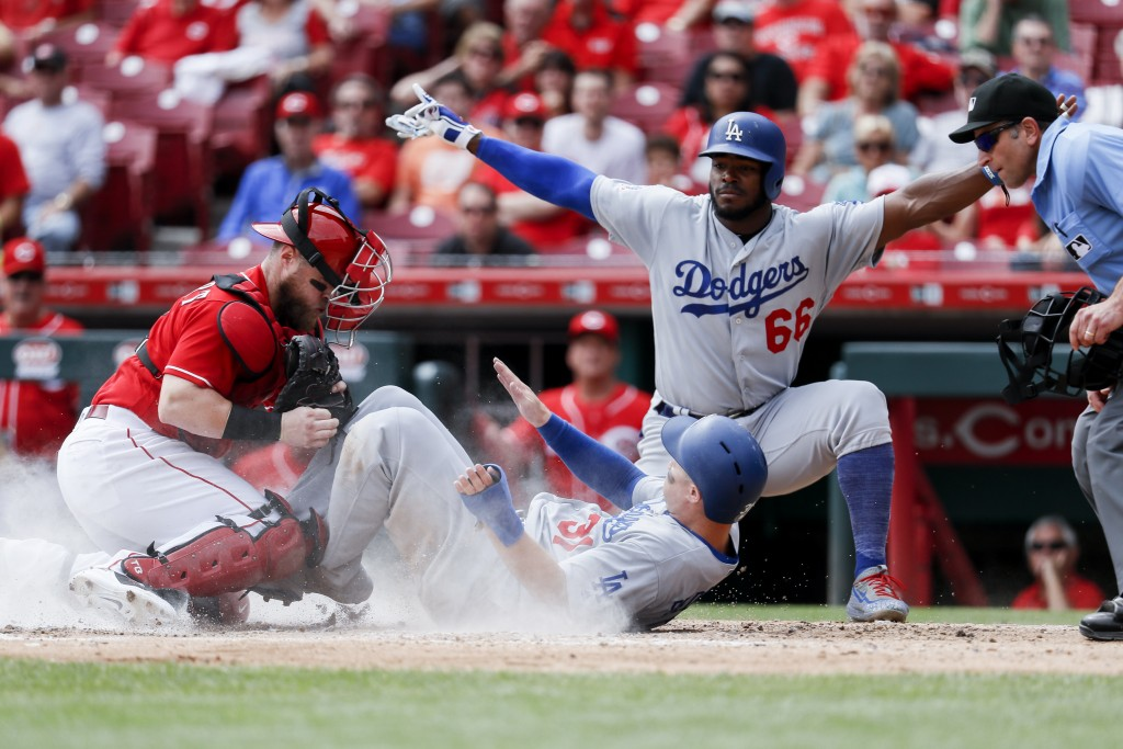 Los Angeles Dodgers' Joc Pederson (31) scores against Cincinnati Reds catcher Tucker Barnhart, left, as Yasiel Puig (66) reacts in the fifth inning of