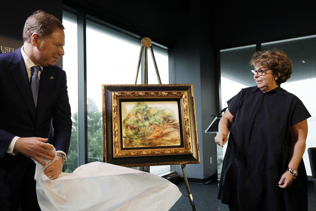 United States Attorney Geoffrey Berman, left, unveils a Renoir painting with Sylvie Sulitzer at a news conference, Wednesday, Sept. 12, 2018, in New Y