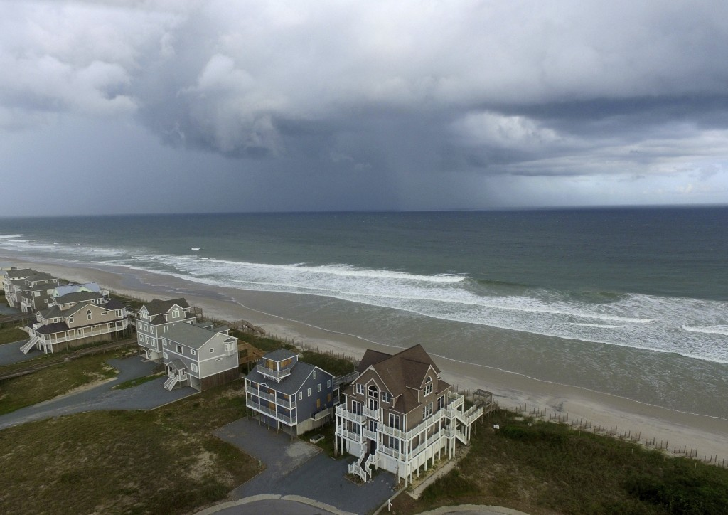 A storm front passes homes in North Topsail Beach, N.C., prior to Hurricane Florence moving toward the east coast on Wednesday, Sept. 12, 2018. (AP Ph