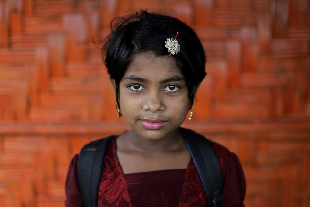 In this June 27, 2018, photo, Nazifa, 10, poses for a portrait in front of her classroom in Chakmarkul refugee camp, Bangladesh. Amid the misery and m
