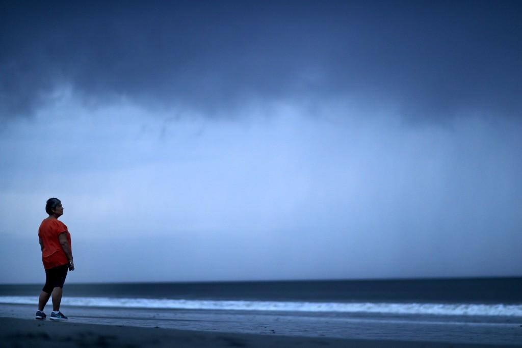 Paula Thibodeau, of Conway, S.C., watches a storm cloud as Hurricane Florence approaches Myrtle Beach, S.C., Thursday, Sept. 13, 2018. (AP Photo/David...