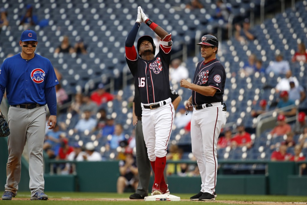 Chicago Cubs first baseman Anthony Rizzo (44), left, and Washington Nationals' first base coach Tim Bogar, right, look on as Nationals' Victor Robles