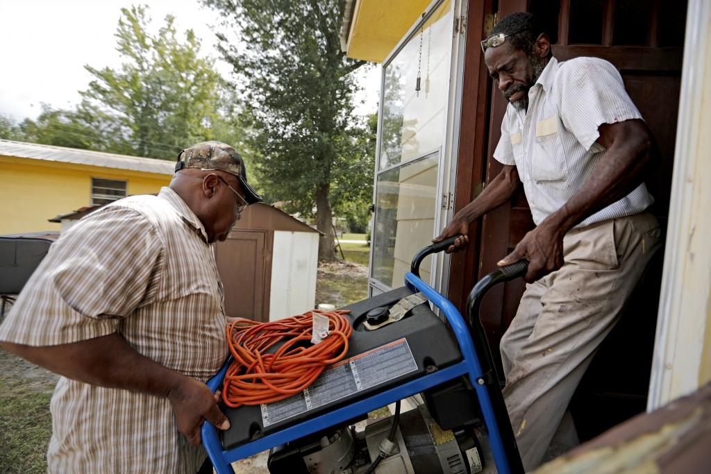 Thomas Lee, left, gets help from Stoney Williamson, right, lifting a generator into his home which flooded two years ago from Hurricane Matthew in Nic