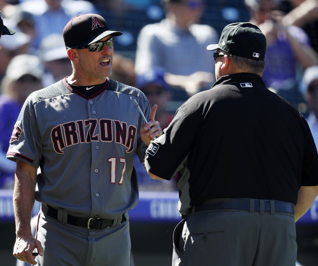 Arizona Diamondbacks manager Torey Lovullo, left, argues with second base umpire Fieldin Culbreth over a call while facing the Colorado Rockies in the