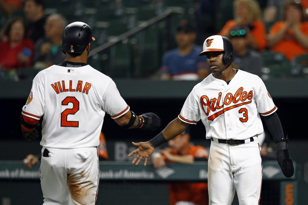 Baltimore Orioles' Cedric Mullins, right, greets teammate Jonathan Villar after they both scored on Tim Beckham's single in the first inning of a base