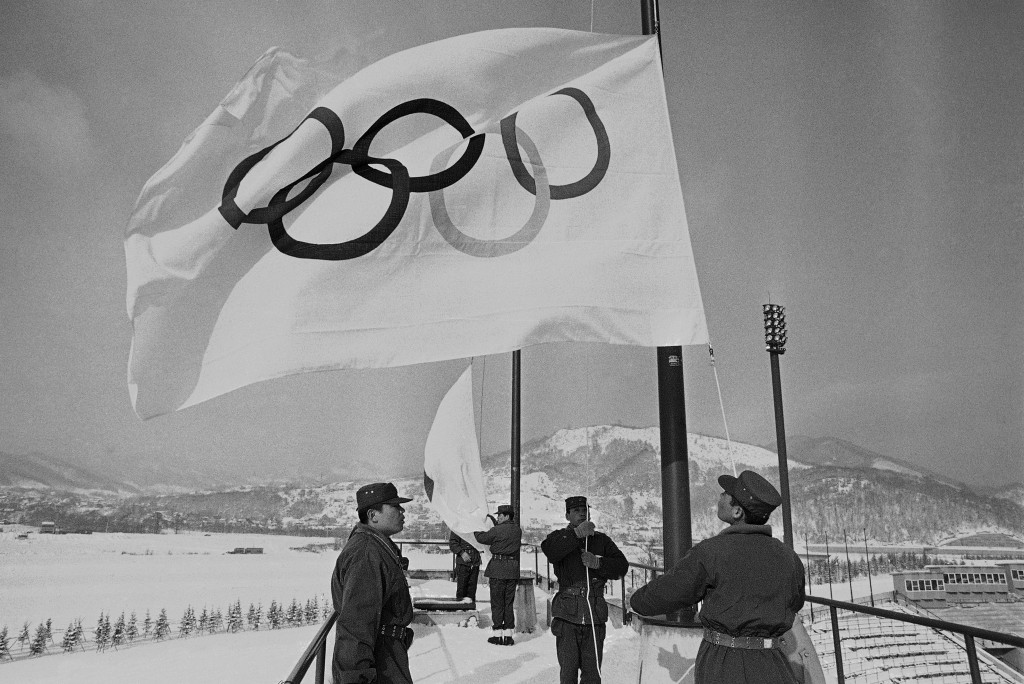 FILE - In this Jan. 23, 1972, file photo, members of Japan's self-defense ground forces raise Olympic Flags in Sapporo at Makomanai speed skating stad