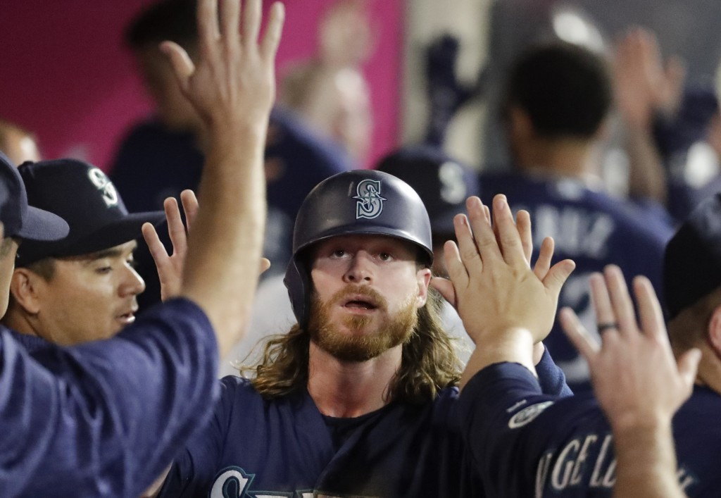 Seattle Mariners' Ben Gamel celebrates in the dugout after scoring on a sacrifice fly by Dee Gordon during the second inning of a baseball game in Ana