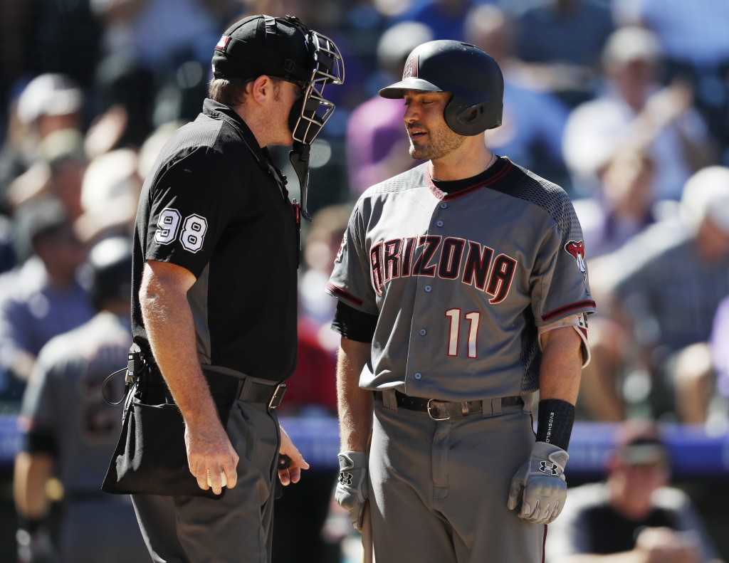 Arizona Diamondbacks' A.J. Pollock, right, confers with home plate umpire Chris Conroy after he called out Pollock on strikes to end the top of in the