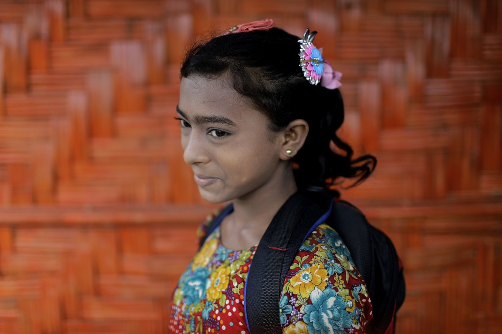 In this June 27, 2018, photo, Wisma Bi Bi, 12, poses for a portrait in front of her classroom in Chakmarkul refugee camp, Bangladesh. Amid the misery
