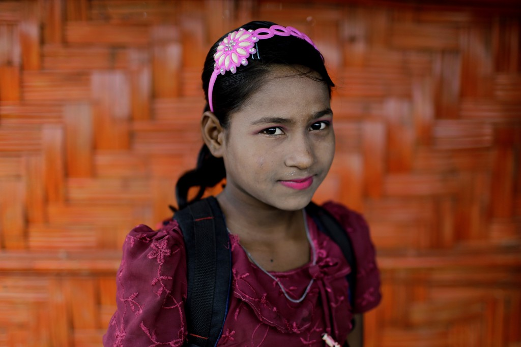 In this June 27, 2018, photo, Shamshoda, 10, poses for a portrait in front of her classroom in Chakmarkul refugee camp, Bangladesh. Amid the misery an
