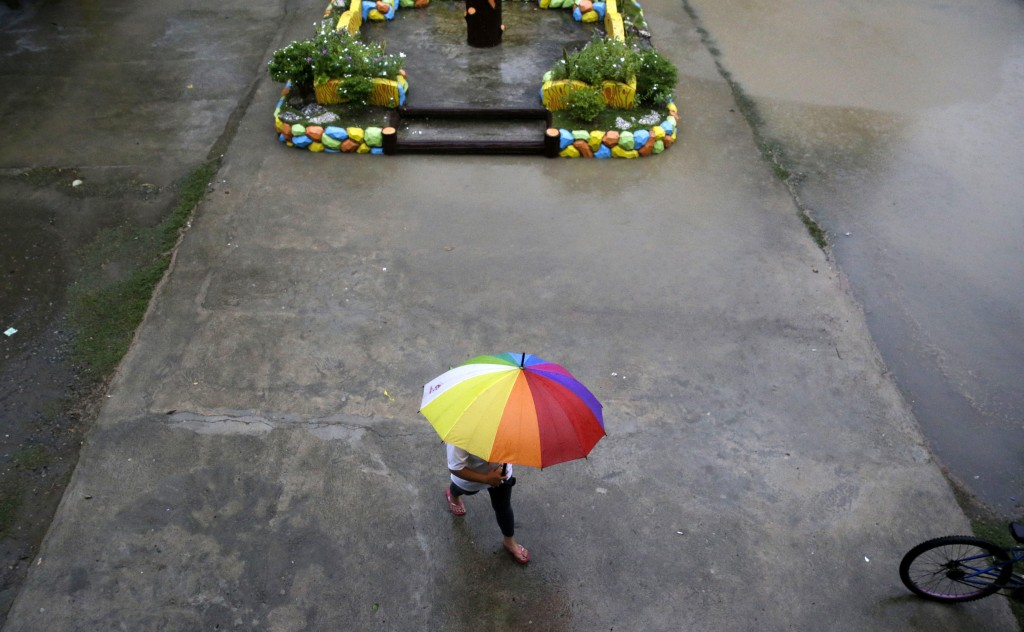 A resident walks as rains from Typhoon Mangkhut begin to affect Tuguegarao city, Cagayan province, northeastern Philippines on Friday, Sept. 14, 2018....
