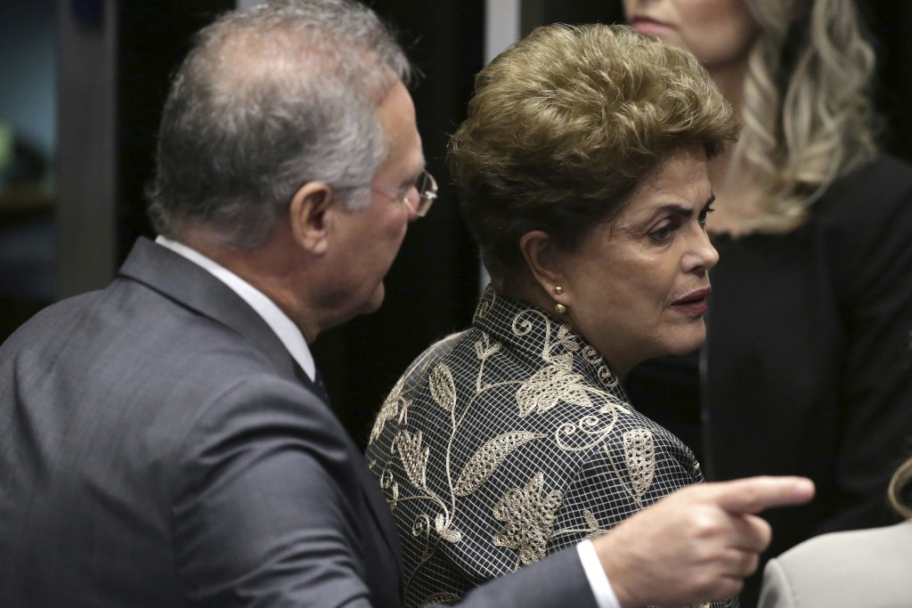 FILE - In this Aug. 29, 2016 file photo, Senate leader Renan Calheiros points to an exit as suspended President Dilma Rousseff looks to leave the Sena