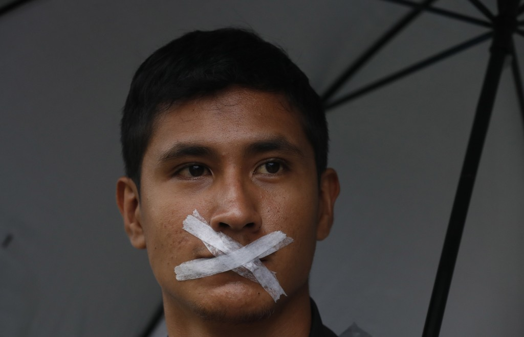 A student with his mouth taped shut participates in the march of silence, along with thousands of other students in protest against groups of institut