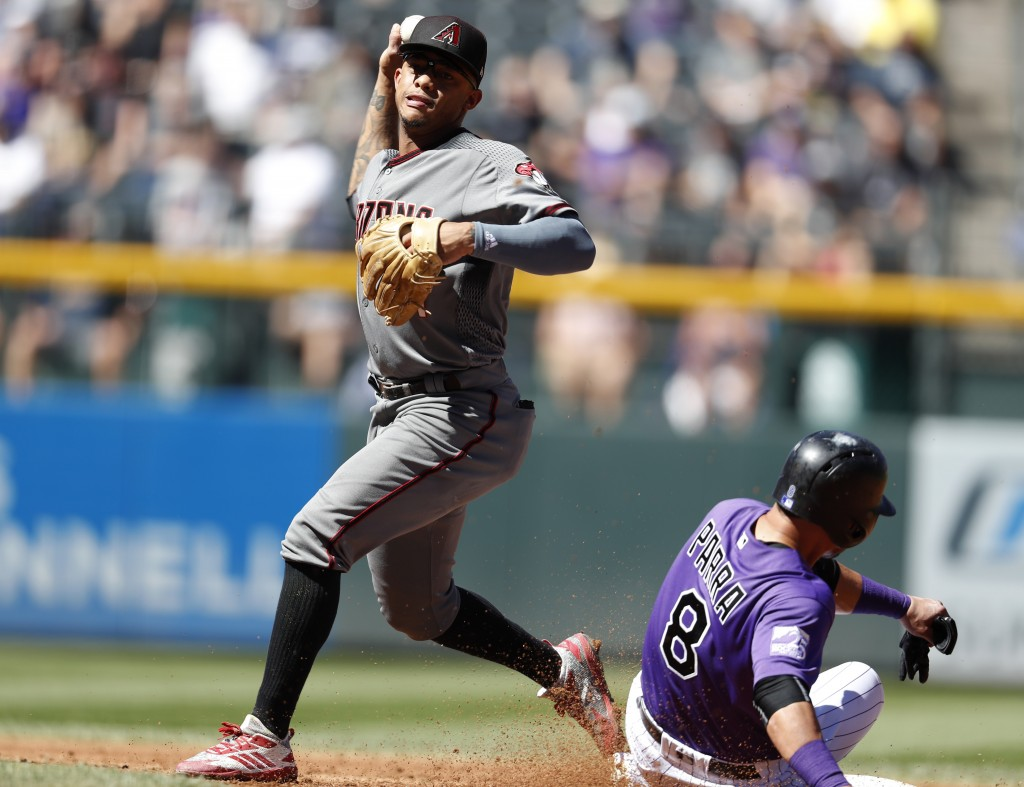Arizona Diamondbacks second baseman Ketel Marte, left, throws to first base after forcing out Colorado Rockies' Gerardo Parra at second base on the fr