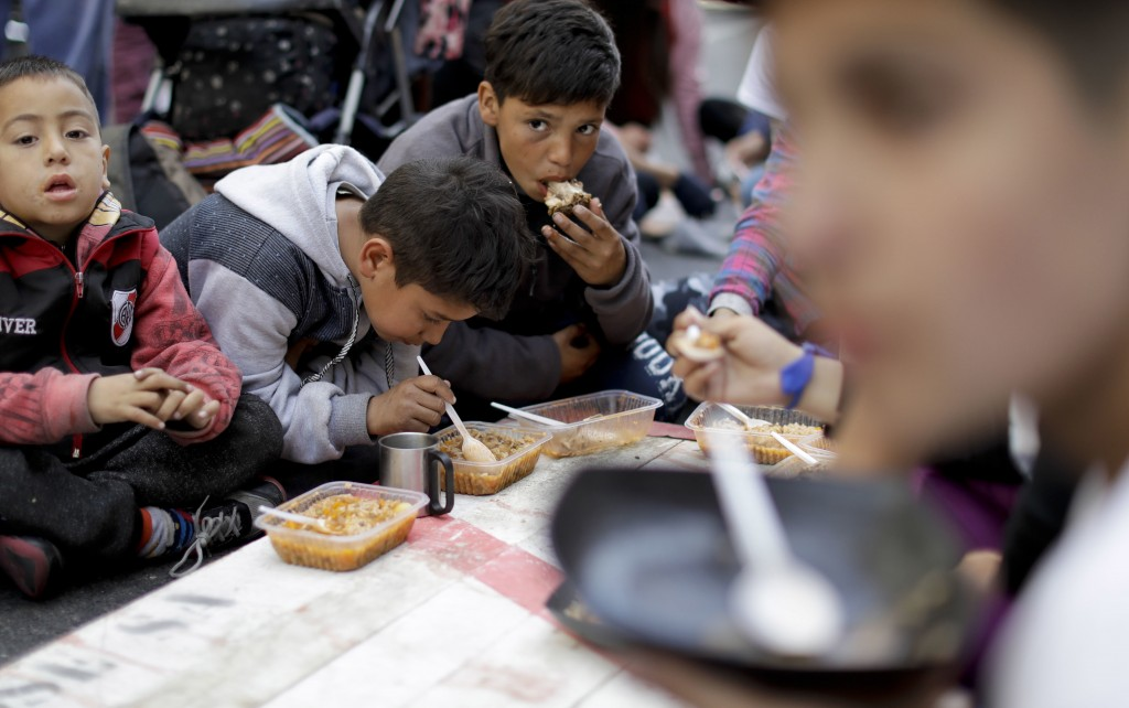 In this Sept. 11, 2018 photo, children eat free food where demonstrators set up a soup kitchen along a main avenue that connects the government house