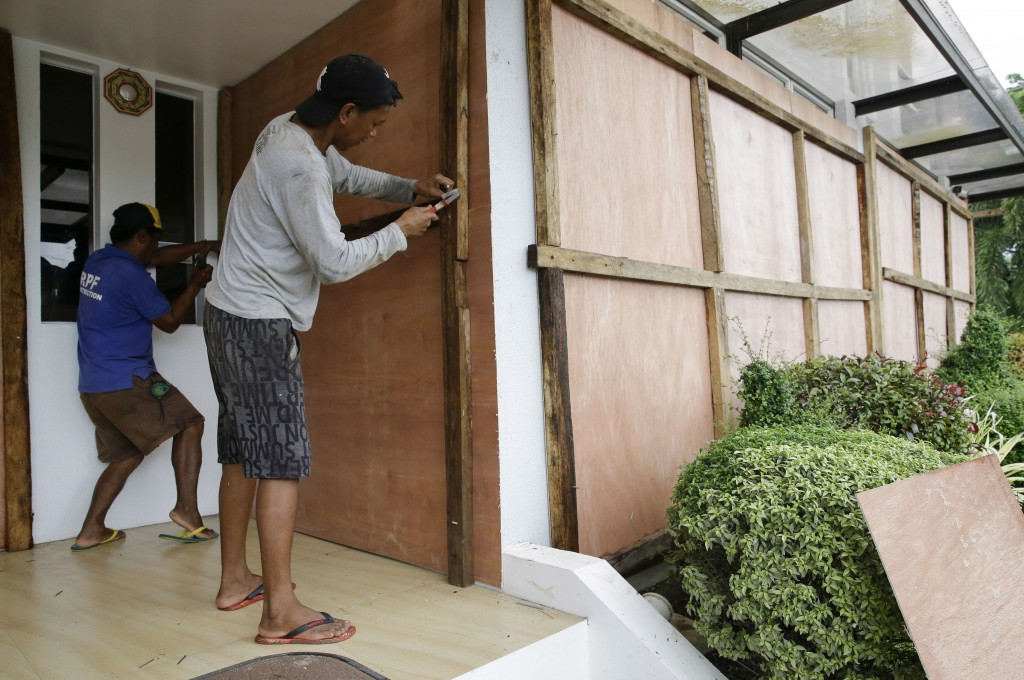 Workers cover windows of a hotel with sheets of plywood as Typhoon Mangkhut nears Cagayan province, northeastern Philippines on Friday, Sept. 14, 2018