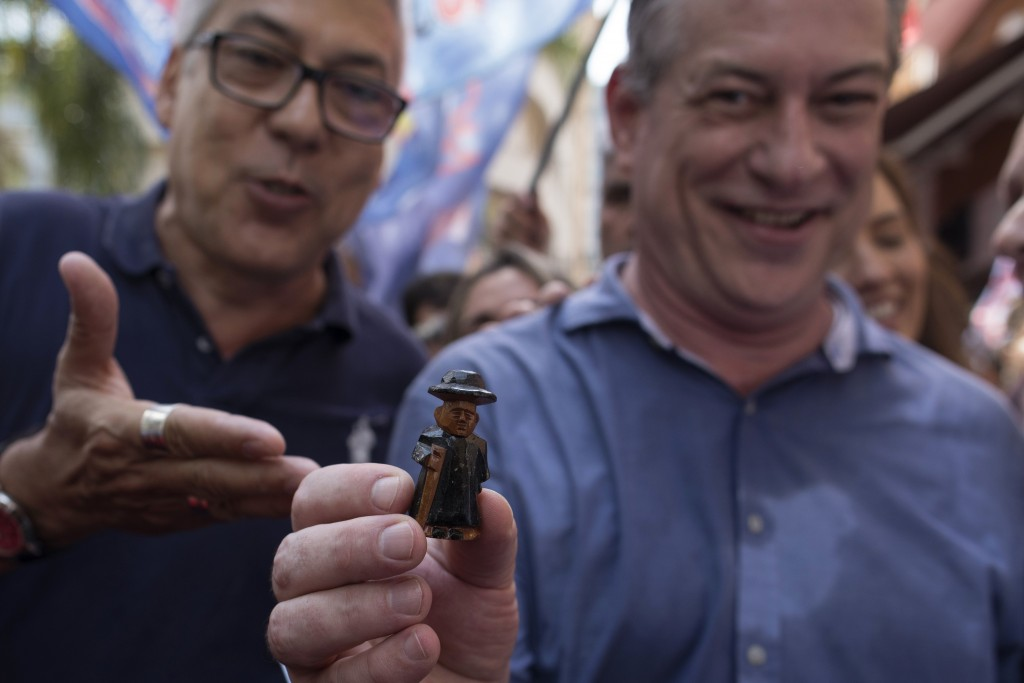 "In this Sept. 12, 2018 photo, Ciro Gomes, presidential candidate with the Democratic Labor Party, holds up a miniature statue of ""Padre Cicero,"" a pri"