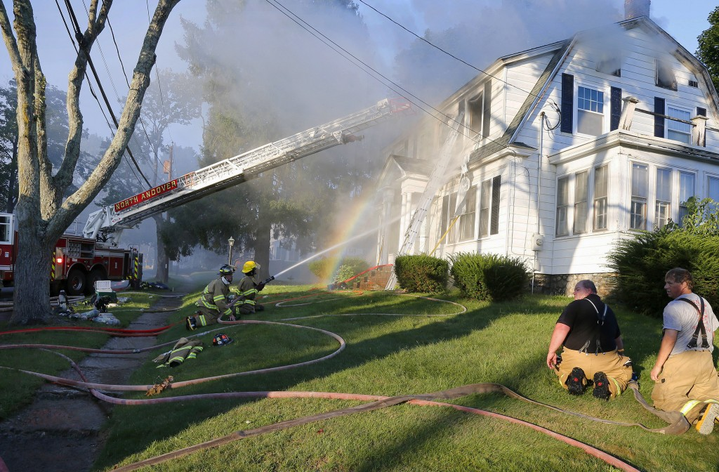 Firefighters battle a house fire, Thursday, Sept. 13, 2018, on Herrick Road in North Andover, Mass., one of multiple emergency crews responding to a s