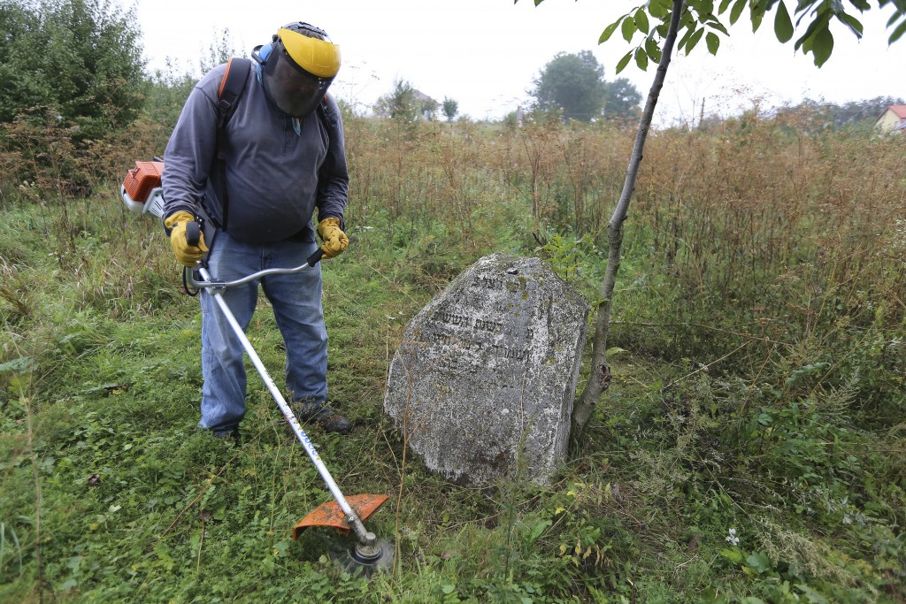 In this photo taken on Aug. 29, 2018, Steven Reece, an ordained Southern Baptist minister who lives near Atlanta cleans an old Jewish cemetery in Roha...