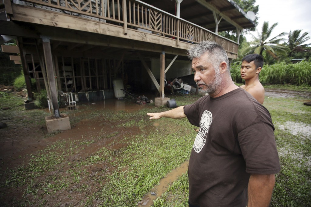 In this Wednesday, Sept. 12, 2018 photo, Honokohau Valley resident Mundy Gillcoat describes to his son how high flood waters raged outside their home