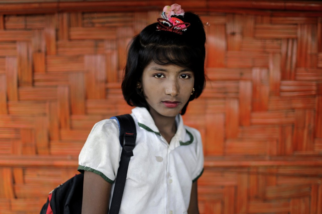 In this June 27, 2018, photo, Dil Kayas, 12, poses for a portrait in front of her classroom in Chakmarkul refugee camp, Bangladesh. Amid the misery an