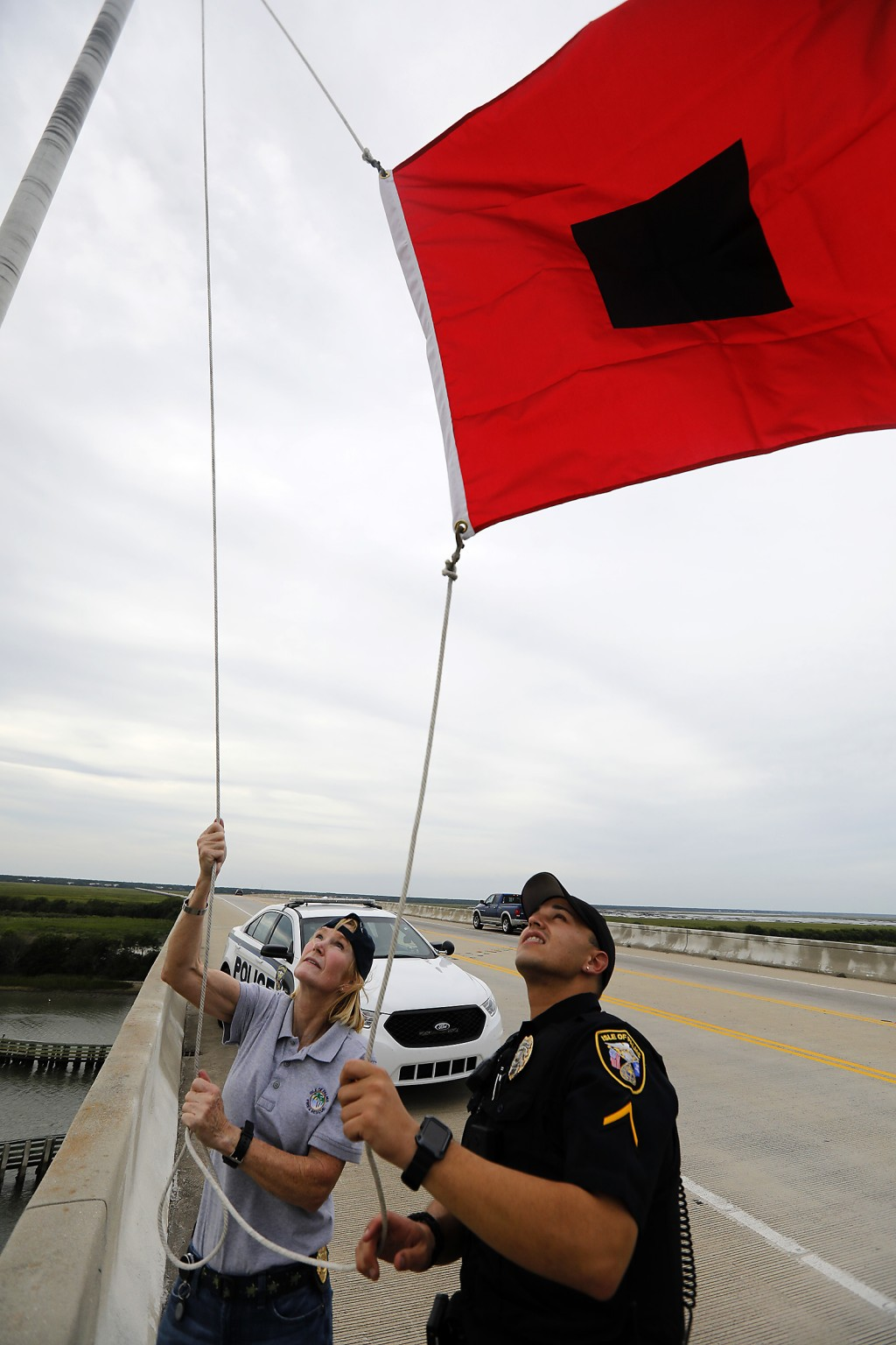 Isle of Palms Fire Chief Ann Graham, at left, and Isle of Palms police officer Thomas Molino III raise a tropical storm warning flag over the Isle of